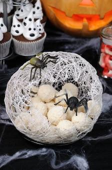 Boules de gaufres en forme d'œufs d'araignée dans un cocon avec une araignée sur la table pour halloween