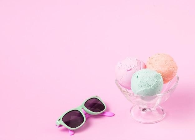 Boules de glace sur un bol en verre près de lunettes de soleil