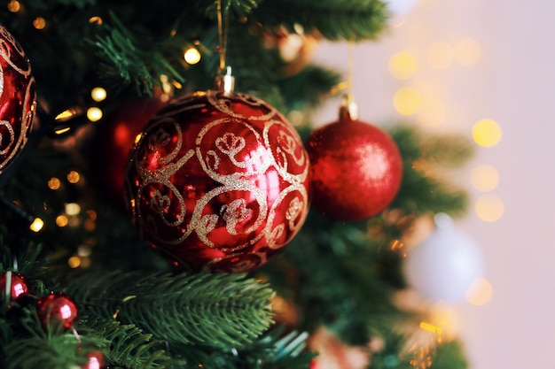 Boules de jouet rouge vif sur l'arbre de noël avec des lumières