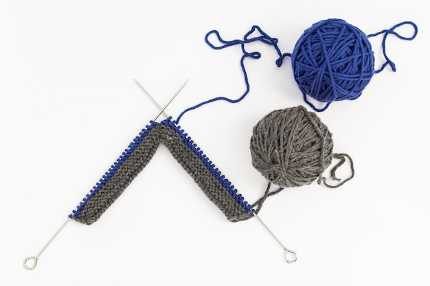 Boules de laine bleu et gris avec des aiguilles à tricoter sur une surface blanche