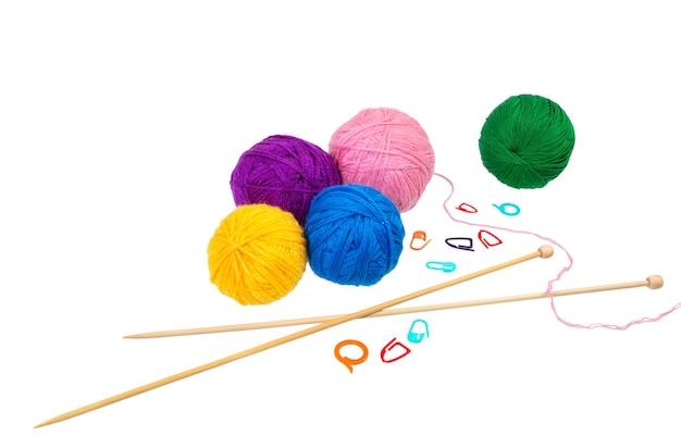 Boules de laine colorées avec aiguilles et clip isolés sur fond blanc.