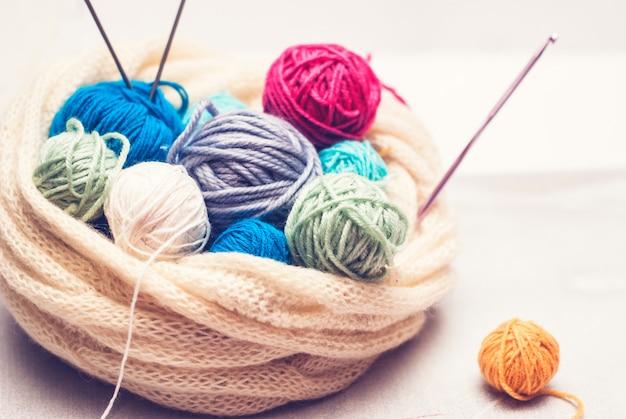 Boules de laine colorées et aiguilles à tricoter sur un fond de bois