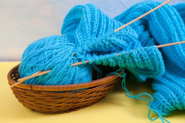 Des boules de laine tricotées et une écharpe bleue se trouvent dans un panier en osier. concept fait à la main.