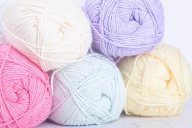 Boules de laine à tricoter dans des tons pastel. des écheveaux de fil de coton pour le tricotage.