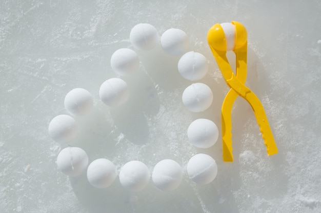 Les Boules De Neige Sont Disposées Sur La Glace En Forme De Cœur à Côté De L'outil De Sculpture De Boules De Neige Photo Premium
