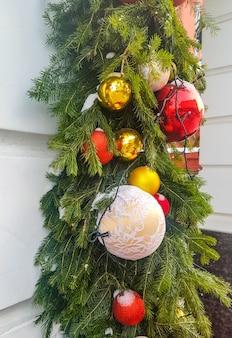Boules de noël accrochées à une branche de sapin, guirlande festive verticale, sur fond de mur, décoration extérieure des bâtiments.