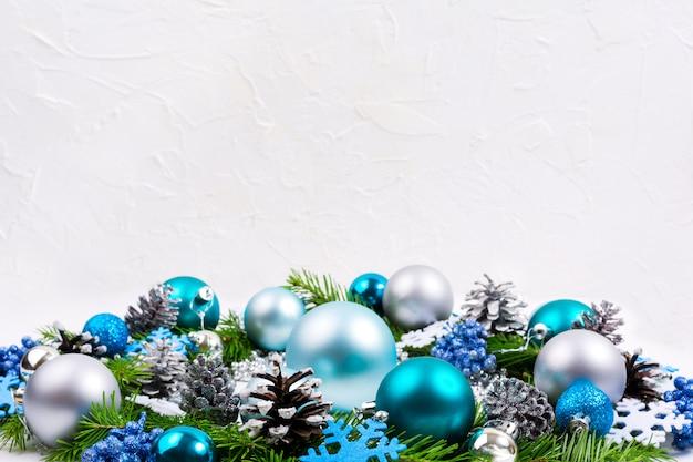 Boules de noël argentées, bleu pâle, turquoise, fond de baies de paillettes, espace de copie.