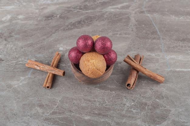 Boules de noël et un biscuit dans un bol à côté de bâtons de cannelle sur une surface en marbre
