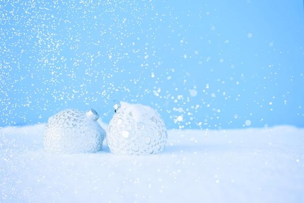 Des boules de noël blanches avec un beau motif se trouvent sur la neige blanche avec des étincelles.