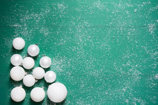 Boules de noël blanches sur fond de bois vert avec de la neige