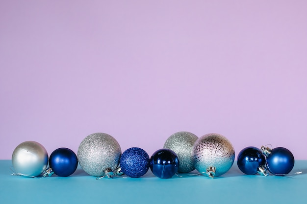 Des boules de noël brillantes aux couleurs bleu, blanc et argent sont disposées en ligne sur un fond turquoise et rose