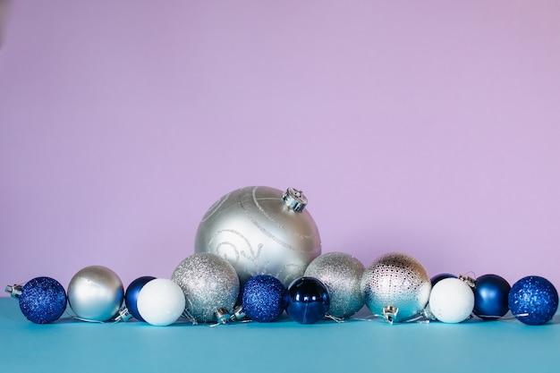 Des boules de noël brillantes de couleurs bleues, blanches et argentées de différentes tailles sont disposées en rangée sur un fond turquoise et rose.