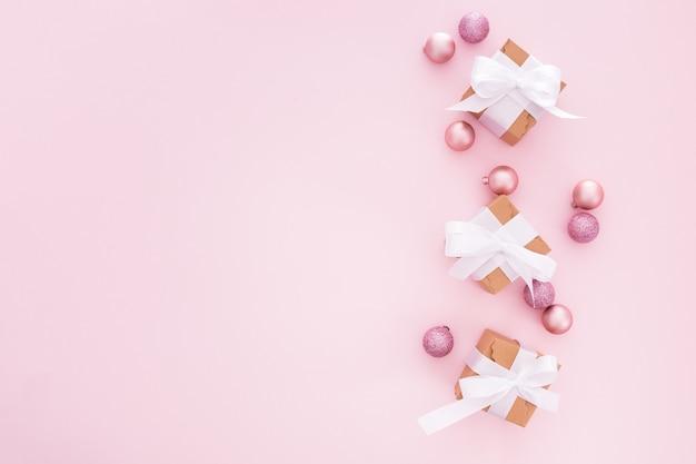 Boules de noël et cadeaux sur fond rose