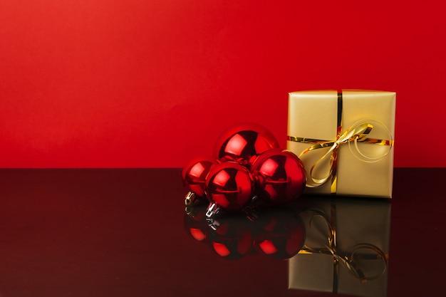Boules de noël et cadeaux sur fond rouge