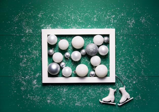 Boules de noël un cadre blanc et patins décoratifs se trouvent sur un fond en bois vert
