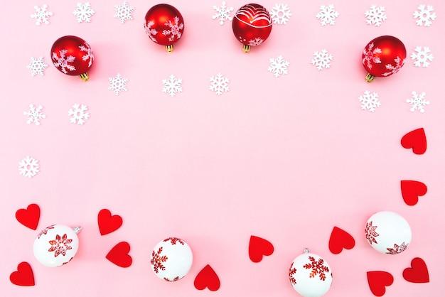 Boules de noël, coeurs rouges et décorations de flocons de neige sur rose
