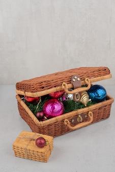 Boules de noël colorées dans le panier avec des biscuits en corde.