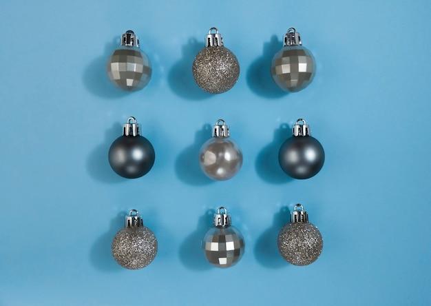 Boules de noël de couleur métallisée sur papier bleu pastel. mise à plat de symétrie festive.