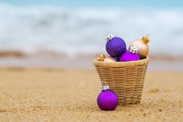 Boules de noël dans un panier sur le rivage sablonneux de l'océan