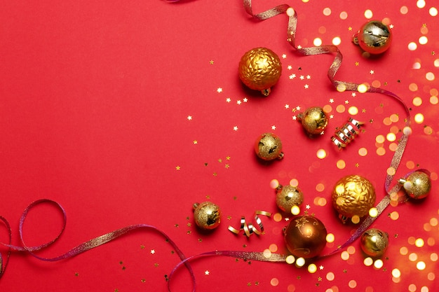 Boules de noël de différentes tailles de couleur or avec des confettis d'étoiles scintillantes, ruban brillant satiné sur fond uni rouge. concept d'idée minimaliste pour la célébration du nouvel an ou de noël.