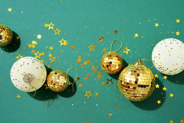 Boules de noël dorées et blanches avec des étoiles brillantes sur fond vert