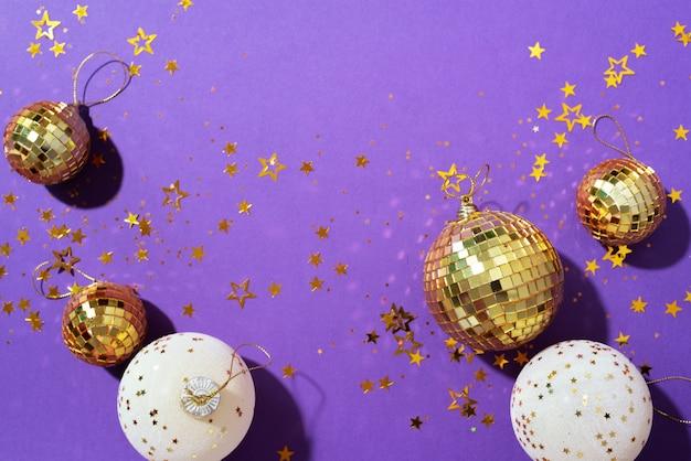 Boules de noël dorées et blanches avec des étoiles brillantes sur fond violet