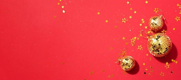 Boules de noël dorées avec des étoiles brillantes sur fond rouge