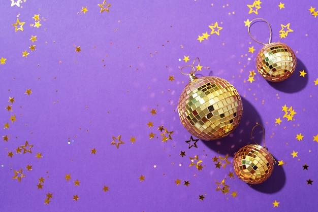Boules de noël dorées avec des étoiles brillantes sur fond violet