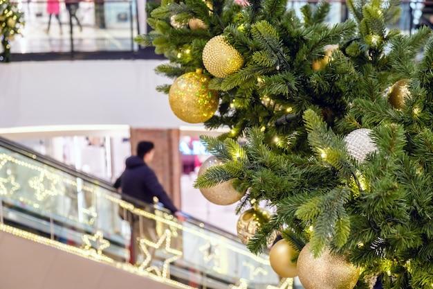 Boules de noël dorées et guirlande sur un sapin décoré dans un centre commercial.