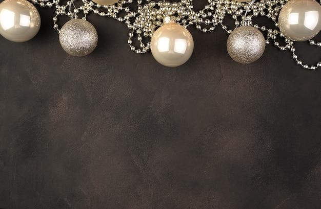 Boules de noël dorées et perles sur fond marron