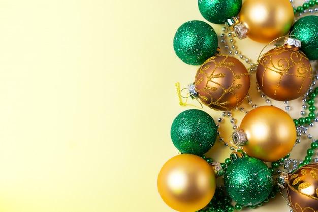 Boules de noël dorées et vertes et décorations sur fond jaune avec espace de copie