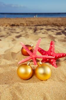 Boules de noël avec des étoiles de mer sur la plage
