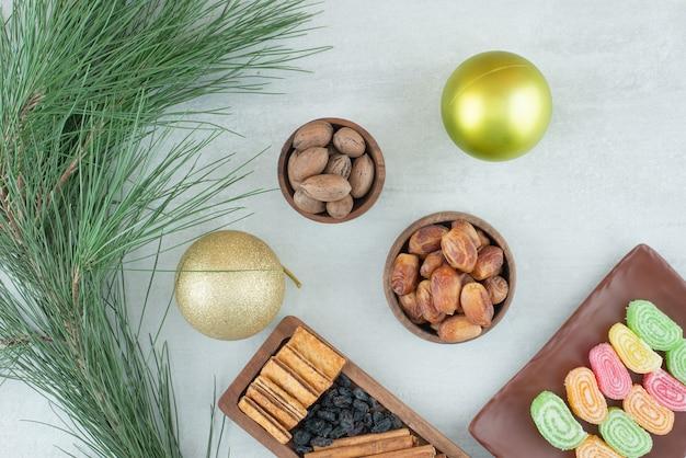 Boules de noël avec des noix et des bonbons sur fond blanc.ch photo de haute qualité