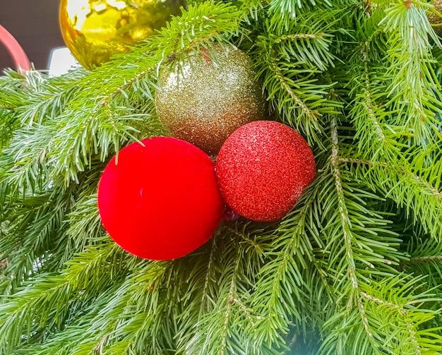 Boules de noël or et rouges sur le gros plan de l'arbre de noël. décorer une maison du nouvel an.