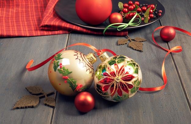 Boules de noël ornés avec motif étoile de noël attaché avec un ruban et une serviette rouge sur bois