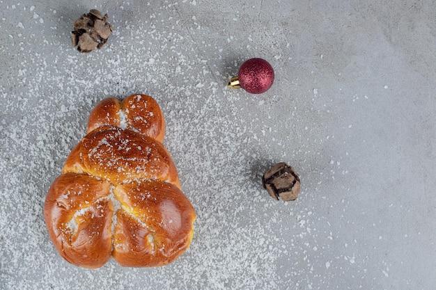 Boules de noël et de pin entourant un petit pain sucré sur une table en marbre.