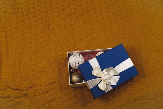 Boules de noël rondes minimalistes blanches et or dans une boîte bleue avec un arc sur une couverture marron chaud avec espace de copie