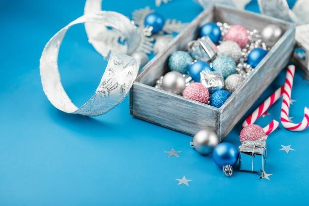 Boules de noël rose, argent et bleu, perles de noël argentées dans une boîte en bois et cannes de bonbon sur bleu