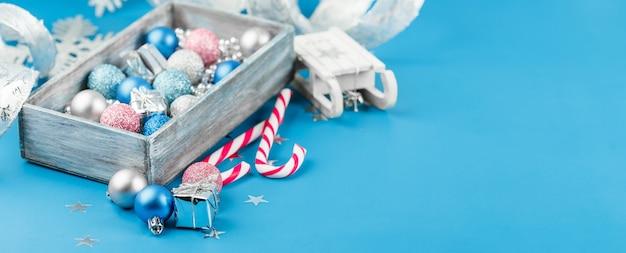 Boules de noël roses, argentées et bleues, perles de noël argentées dans une boîte en bois et cannes à sucre sur bleu, longue et large bannière