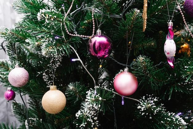 Des boules de noël roses sont accrochées à l'arbre. espace de copie