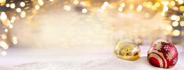 Boules de noël rouge vif sur la neige sur fond d'or avec bokeh et chutes de neige