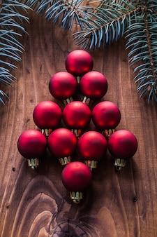 Boules de noël rouges en forme de sapin et de branches planche de bois vintage firtree