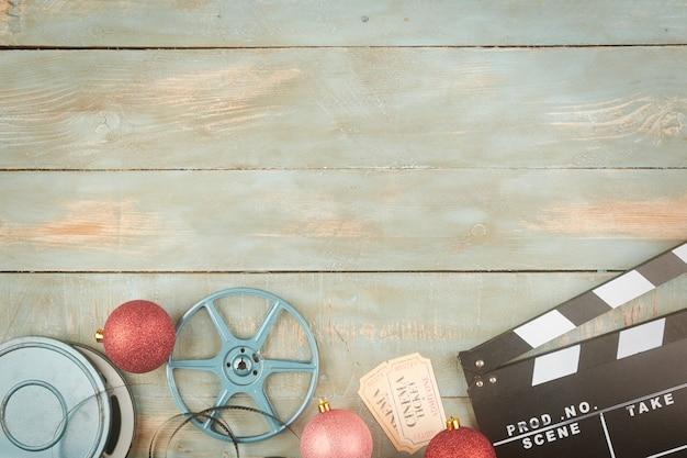 Boules de noël rouges et objets de cinéma sur fond de bois