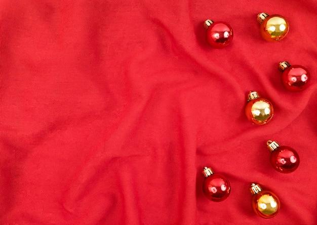 Boules de noël rouges et or sur fond textile rouge.