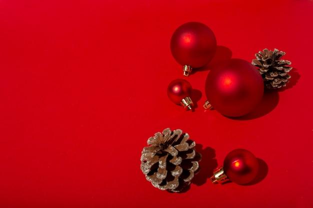 Boules de noël rouges et pommes de pin sur table rouge