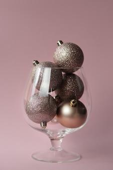 Les boules de noël se trouvent dans un vase en verre sur un mur rose