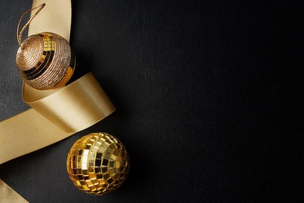 Boules d'or de noël sur fond noir. mise à plat.