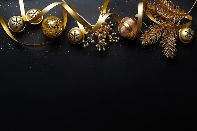 Boules d'or de noël sur fond sombre. mise à plat.