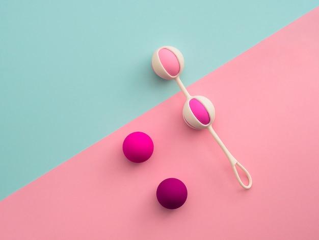 Boules d'orgasme rose, boules de geisha sur fond rose et bleu