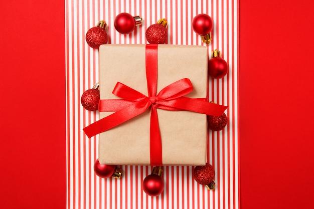 Boules de paillettes de noël rouge et cadeau de papier kraft sur fond rouge.